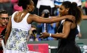 Venus Williams (L) and Serena Williams move to embrace after their Indian Wells third-round fixture.