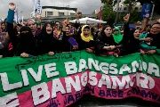 Filipino Muslims shout after hearing the Comprehensive Agreement on the Bangsamoro was signed in Mendiola Bridge, near the Malacanang presidential palace in Manila, the Philippines, 27 March 2014.