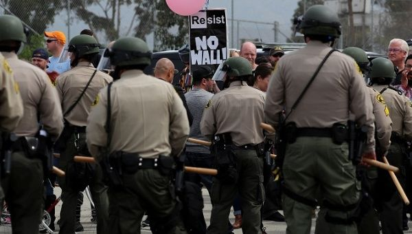 A large police presence watches over protesters and supporters during the visit of U.S. President Donald Trump to view border wall prototypes in San Diego, California, U.S., March 13, 2018.