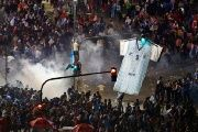 Argentina's fans run away from tear gas as they clash with riot police in Buenos Aires after Argentina's World Cup loss to Germany