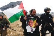 Palestinian activist holds a picture of late South African President Nelson Mandela during a protest in the West Bank.
