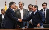 Delegates from the Colombia government and the Leftist ELN shake hands after resuming talks in Quito, Ecuador.