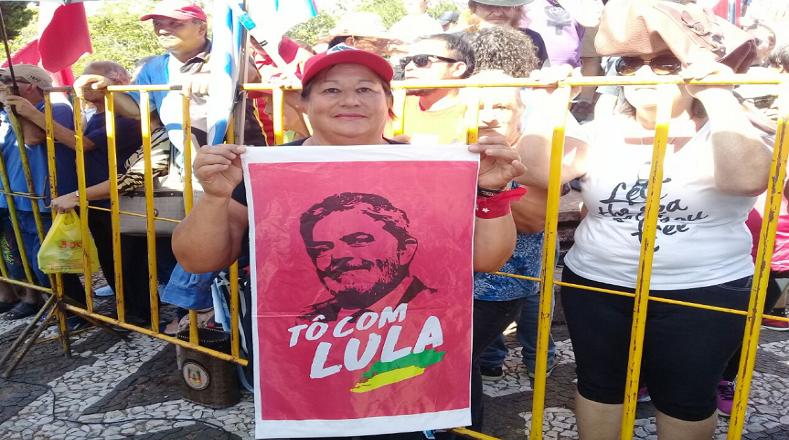 Una mujer sostiene un pendón con la cara de Lula da Silva.