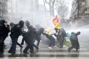 French riot police use water cannons during clashes with masked protesters attending a demonstration during a national day of strike against reforms in Paris.