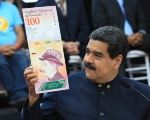 Venezuela's President Nicolas Maduro holds a sample of the new hundred bolivars notes during a meeting with the ministers responsible for the economic sector at Miraflores Palace in Caracas, Venezuela March 22, 2018.