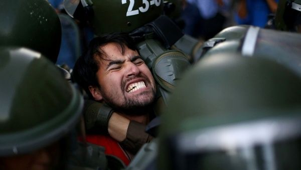 A demonstrator is detained during a protest demanding an end to profiteering in the education system in Santiago, Chile, March 27, 2018.