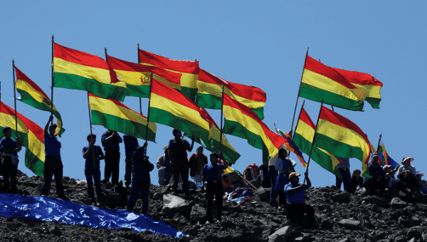 Bolivians hold their national flags as they watch a re-enactment of a War of the Pacific battle.