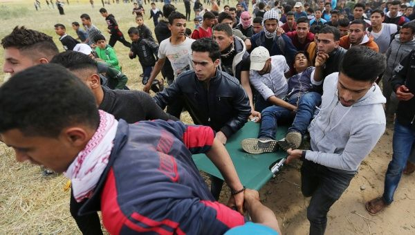 A wounded Palestinian is evacuated during clashes with Israeli troops, during a tent city protest along the Israel border with Gaza, demanding the right to return to their homeland, the southern Gaza Strip March 30, 2018.
