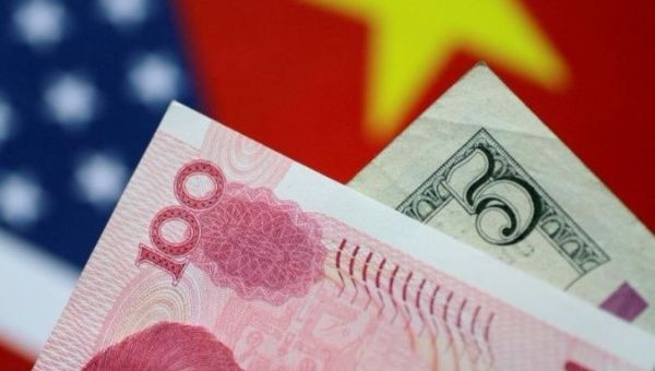 A Chinese yuan is positioned in front of a U.S. dollar.