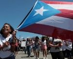 Students of the University of Puerto Rico wave the flag of their Island during a protest.