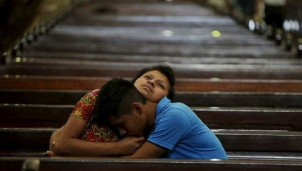 A couple embrace each other while sitting in the pews of a cathedral in Guatemala City.