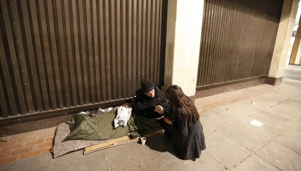 A homeless man grasps the hand of a volunteer, who was handing out donated clothing, near Victoria rail station in central London.