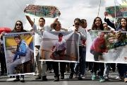 Relatives and friends hold pictures of Ecuadorean journalists who were kidnapped near the Colombian border, during a protest march to demand for their release, in Quito.