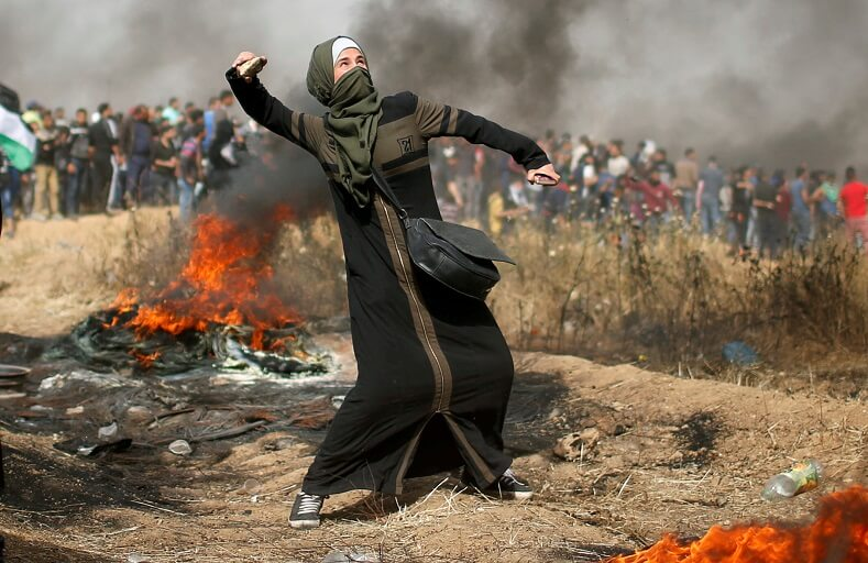 Woman hurls stone at Israeli snipers.