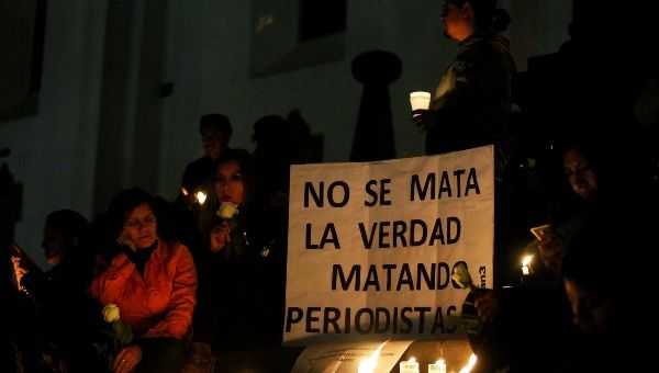 "People participate in a vigil for two Ecuadorean journalists and their driver in Quito, Ecuador April 13, 2018. The sign reads, ""You don"