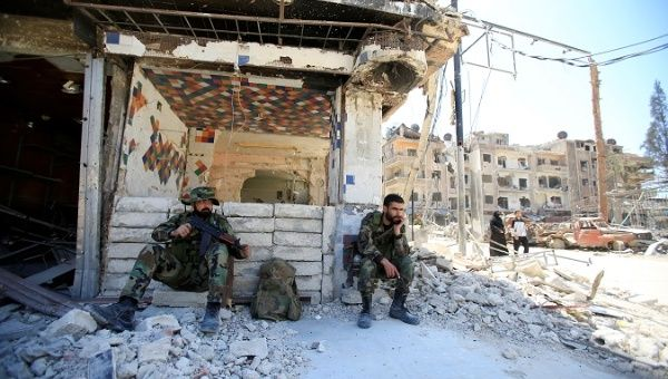 Members of Syrian police sit at a damaged building at the city of Douma, Damascus, Syria April 16, 2018.