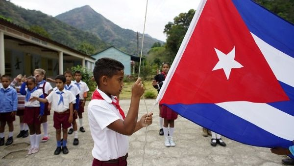 A boy raises the Cuban flag during a daily ceremony held at a school in the village of Santo Domingo, in the Sierra Maestra, Cuba, April 2, 2018.