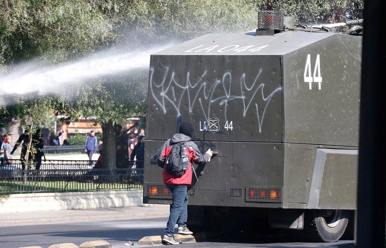 A protester spray paints a riot police vehicle.