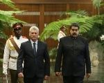 Cuban President Miguel Diaz-Canel (L) and Venezuela's President Nicolas Maduro review an honour guard during a ceremony at the Revolution Palace in Havana, Cuba April 21, 2018.