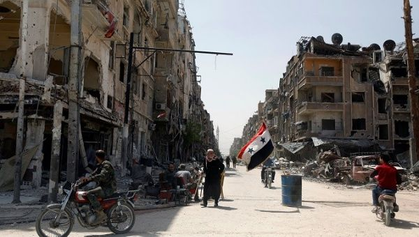A Syrian flag flutters in the wind on a war-ravaged street in the city of Douma in Damascus, Syria.