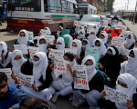 Schoolgirls holding placards sit in a road during a protest against the rape of several minor girls, in Srinagar April 17, 2018.