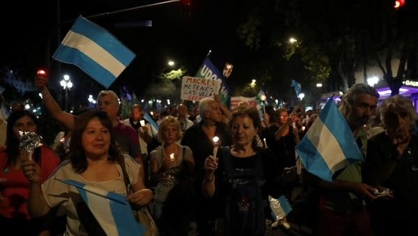 Demonstrators hold candles and wave Argentine national flags during a protest against utility rate hikes in Buenos Aires, Argentina, April 19, 2018.