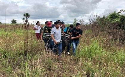 Police carry the body of Sebastian Woodroffe, who was beaten and strangled in Ucayali on Friday after being accused of killing a revered medicine woman,