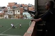 Boys play football as an armed soldier looks on in Mare Favela Complex in Rio de Janeiro, Brazil.