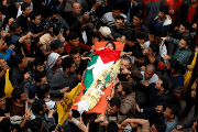 Mourners carry the body of Palestinian Azam Ewidah,15, who was killed by Israeli sniper fire.