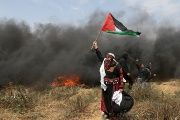 A woman demonstrator holds a Palestinian flag during clashes with Israeli troops at a protest at the Israel-Gaza border, April 27, 2018.