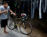 Palestinian cyclist and amputee Alaa Al-Dali, 21, stands next to his bicycle at his house in Rafah.
