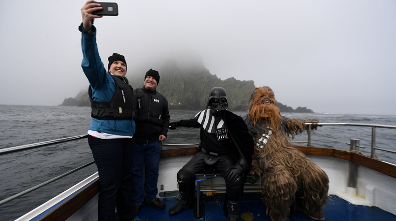 "Darth Vader y Chewbacca disfrutan de un viaje en barco a la isla Skellig, Irlanda, durante el festival inaugural ""May The 4th Be With You"", mientras los turistas se toman autofotos con ellos."
