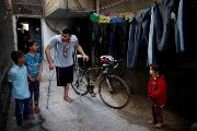 Palestinian cyclist Alaa Al-Daly, who lost his leg by a bullet fired by Israeli troops, talks with his sister while holding his bicycle at his house in Gaza Strip.