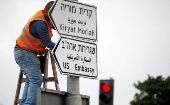 A worker hangs a road sign directing to the U.S. embassy, in the area of the U.S. consulate in Jerusalem, May 7, 2018.