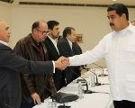 President Nicolas Maduro (R) shakes hands with Jesus Torrealba (L), former secretary of Venezuela's coalition of opposition parties in Caracas in 2016.