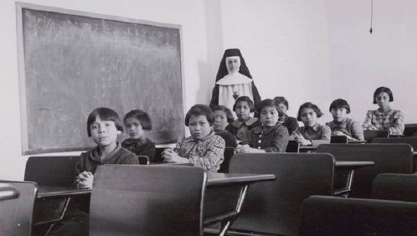 A group of female students and a nun pose in a classroom at Cross Lake Indian Residential School in Cross Lake, Mba., in a February, 1940.