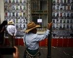 A man sees the pictures of about 40,000 people that went missing during the Guatemalan civil war. House of Memory, Guatemala City, May 10, 2018.