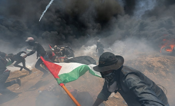 Palestinian demonstrators run for cover from Israeli fire during a protest against U.S. embassy move to Jerusalem at the Israel-Gaza border in the southern Gaza Strip.