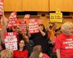 Protesters hold placards during a city council vote for a new tax on the city's biggest companies as a way of fighting a housing crisis sponsors attribute largely to a local economic boom driving real estate costs, in Seattle, Washington, U.S., May 14, 2018.