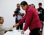 Venezuela's President Maduro greets a worker at a polling station in Caracas during the May 20 elections.