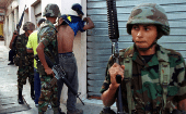 Honduran soldiers search a suspect for gang-related tatoos in Tegucigalpa, 2001.