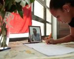 A student writes in a book of condolences dedicated to her classmate Jose Carlos Figueroa, shown in the picture beside the book, at the University of Havana, Cuba.