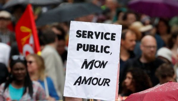 """Public Service, My Love,"" reads a banner during a march by public sector workers in Paris"