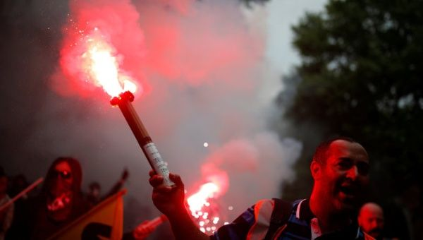 A protester holds a safety flare during the demonstration for a national day of strikes by public sector workers in Paris