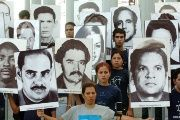 Cubans carry portraits of Posada Carriles' victims.