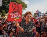 Former Brazilian President Dilma Rousseff holds up a poster that reads,