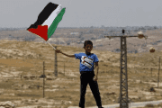 A Palestinian Bedouin boy holds a Palestinian flag during a protest against Jewish settlements in Susya village south of the West Bank city of Hebron.