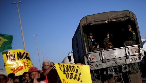 A truck carrying army officials passes by people supporting the truck owners striking in protest against high diesel prices in Luziania, Brazil May 27, 2018.