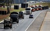 Army officers escort trucks which supplied aviation gasoline to the International Brasilia Airport.