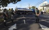 Policemen take position as a fuel truck arrives at a gas station in Porto Alegre, Brazil.